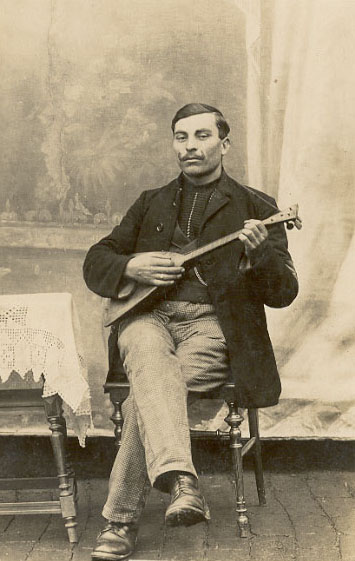 Mustached man with balalaika (1910s photo)